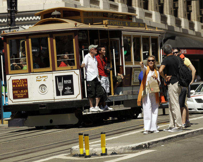 FILE - In this Sept. 1, 2010 photo, visitors wait to board a cable car in San Francisco's Union Square. In this city of innumerable tourist attractions, the clanging cable cars stand out as a top draw. They also stand out for the inordinate number of accidents and the millions of dollars annually the city pays out to settle lawsuits for broken bones, severed feet and bad bruises caused when 19th Century technology runs headlong into 21st Century city traffic and congestion. Recently, five passengers and two workers were injured after an inch-long bolt in the track caused their cable car to slam to a sudden stop. (AP Photo/Marcio Jose Sanchez)