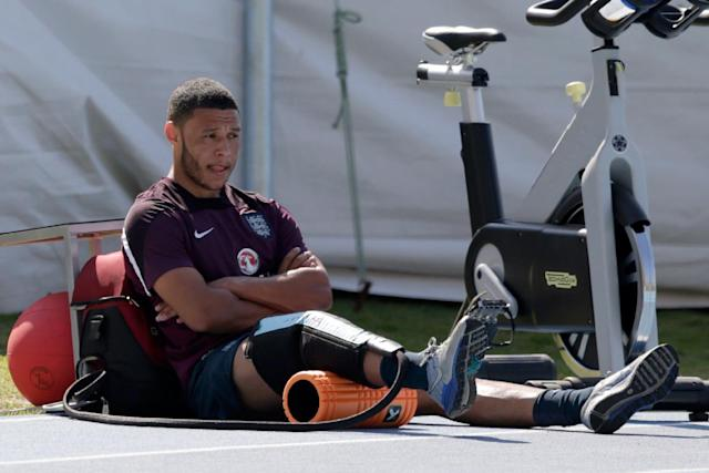 England's Alex Oxlade-Chamberlain sits down after performing some running exercises whilst training away from the rest of the squad as he continues to recover from a knee injury during a squad training session for the 2014 soccer World Cup at the Urca military base in Rio de Janeiro, Brazil, Monday, June 9, 2014. (AP Photo/Matt Dunham)
