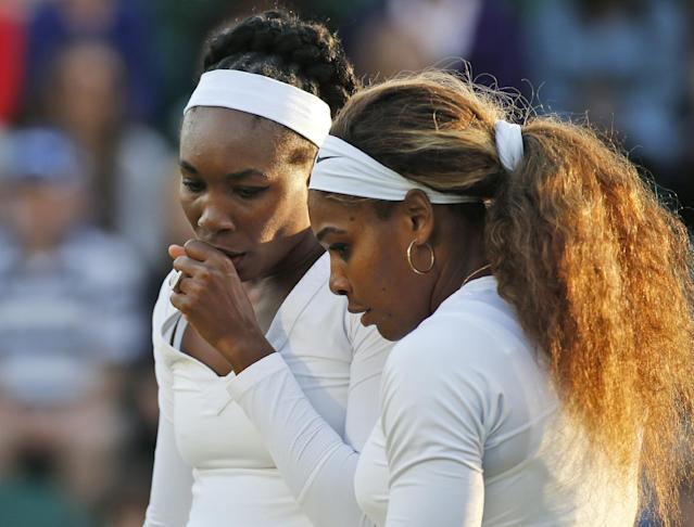 Serena Williams of the U.S., right, talks with her sister Venus Williams of the U.S., left, as they prepare to serve during a doubles match against Oksana Kalashnikova of Georgia and Olga Savchuk of Ukraine at the All England Lawn Tennis Championships in Wimbledon, London, Wednesday, June 25, 2014. (AP Photo/Alastair Grant)