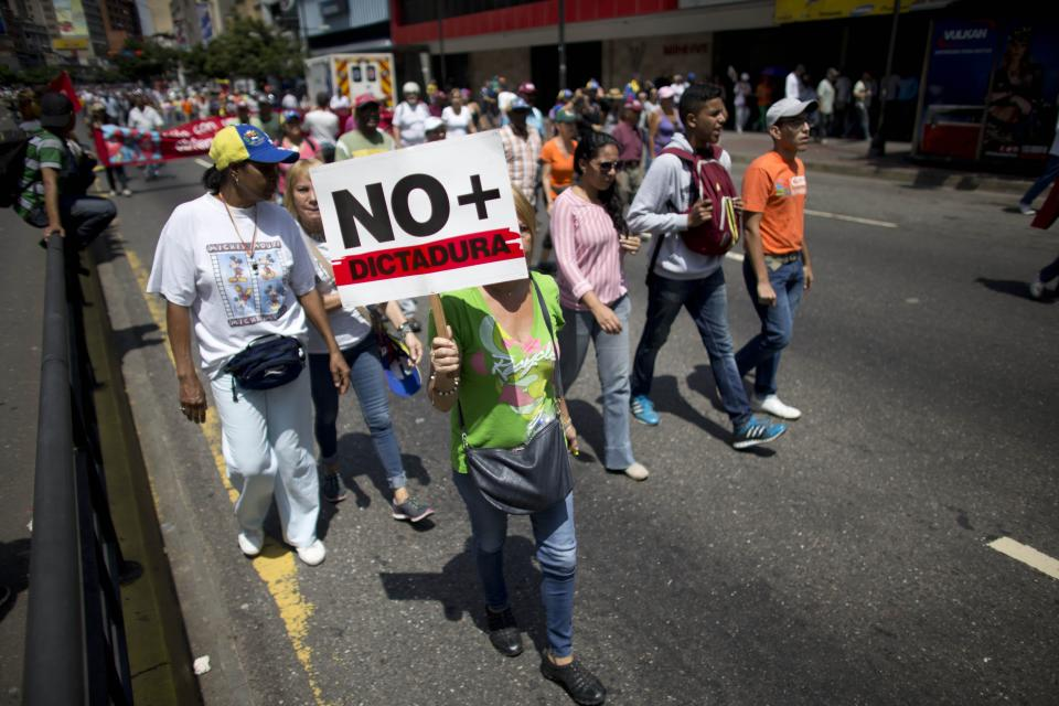 """A woman holds up a sing that in Spanish read """"No more dictatorship"""" as they walk along to gather for a demonstration against President Nicolas Maduro in Caracas, Venezuela, Saturday, April 8, 2017. Opponents of President Nicolas Maduro are preparing to flood the streets of Caracas on Saturday as part of a week-long protest movement that shows little sign of losing steam. (AP Photo/Ariana Cubillos)"""