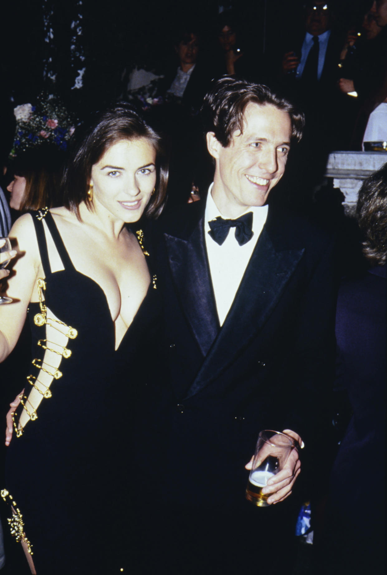 Elizabeth Hurley, famously wearing a Versace dress held together with gold safety pins, and Hugh Grant in 1994 in London. (Photo: Comic Relief/Comic Relief via Getty Images)