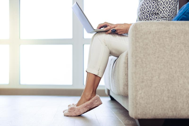 Homely atmosphere. Close up of female hands in fluffy slippers while being at home