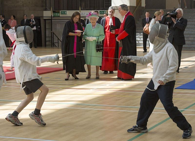 Queen Elizabeth II watches pupils fencing at the sports centre that she officially opened at Westminster School in London on June 12, 2014.