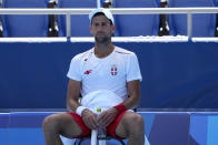 Novak Djokovic, of Serbia, cools off during practice for the men's tennis competition at the 2020 Summer Olympics, Thursday, July 22, 2021, in Tokyo. (AP Photo/Charlie Riedel)
