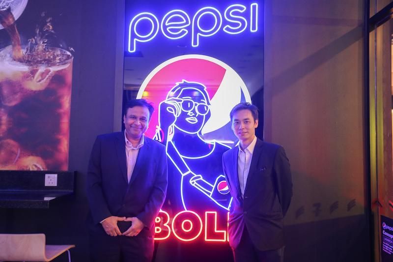 Etika Holdings chief executive officer for Malaysia, Singapore, and Brunei Khalid Alvi (left) and 7-Eleven Malaysia co-chief executive officer Wong Wai Keong posing with one of the store's neon signs. — Picture by Ahmad Zamzahuri
