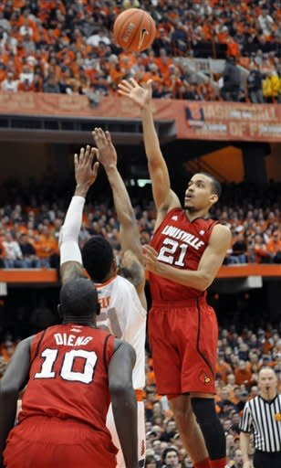 Louisville's Jared Swopshire (21) shoots over Syracuse's Fab Melo during the first half of an NCAA college basketball game in Syracuse, N.Y., Saturday, March 3, 2012. (AP Photo/Kevin Rivoli)
