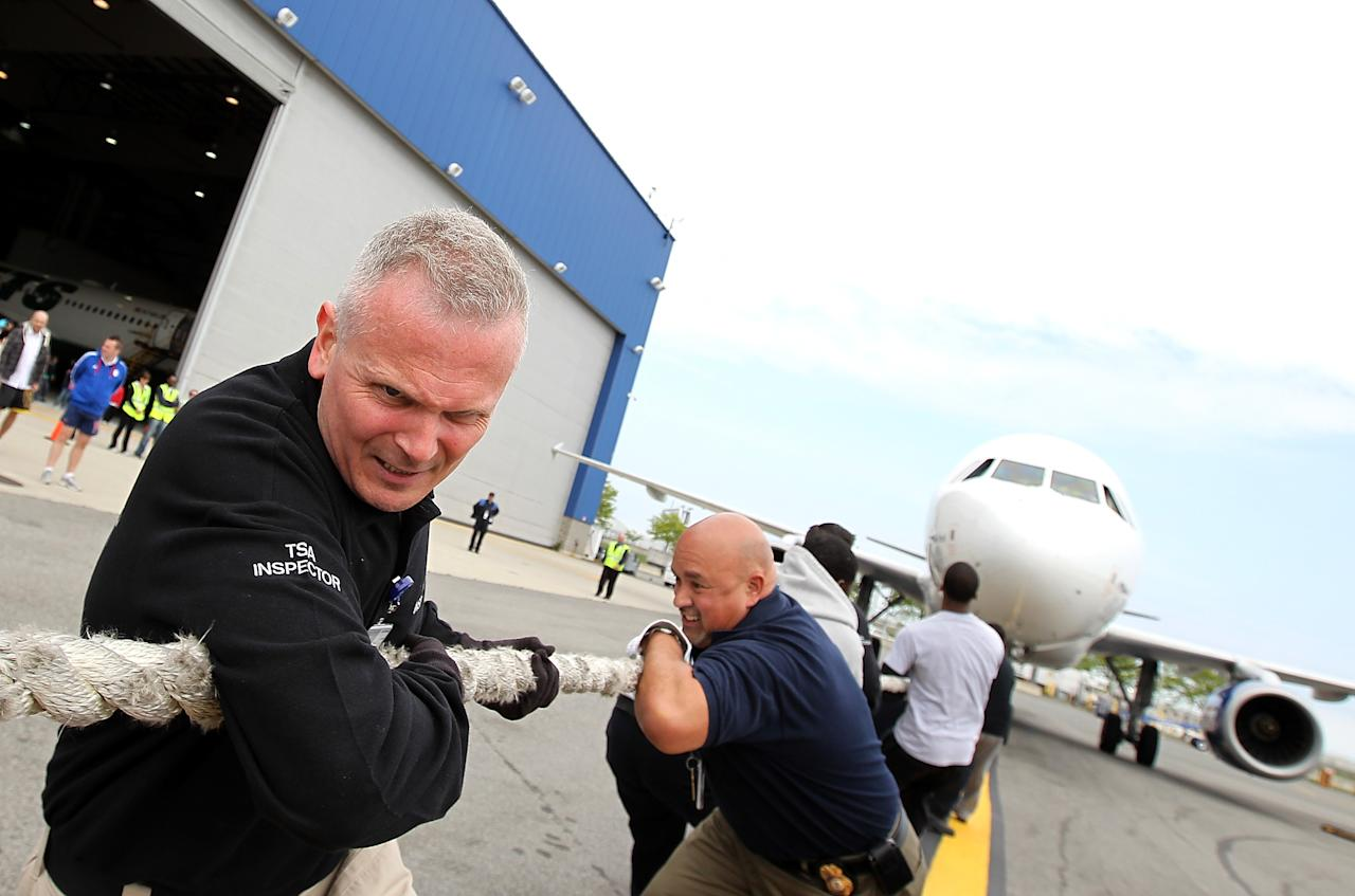 "Members of the TSA pull a Jet Blue A320 plane 100 feet during the third annual Jet Blue Airbus A320 Plane Tug at JFK Airport on May 7, 2012 in New York City. Members of the London's Metropolitan Police Services went head-to-head with local law enforcement and airport crewmembers to see which team of up to 16 people could pull a 150,000 pound Jet Blue A320 aircraft 100 feet in the fastest time. A team of TSA employees had the fastest time of 32 seconds. The ""Brits VS Yanks"" competition raises money and awareness for the Joining Against Cancer Kids (JACK) Foundation, a UK based organization that rase money for Neuroblastoma cancer research.  (Photo by Justin Sullivan/Getty Images)"