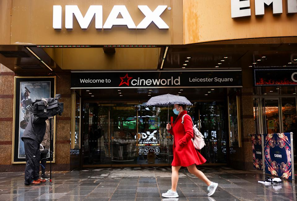 A woman holds an umbrella as she walks past a Cineworld in Leicester's Square in London, Britain, October 4, 2020. Photo: Henry Nicholls/Reuters