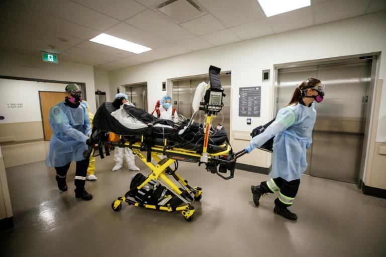 Paramedics and health care workers transfer a patient from Humber River Hospital's Intensive Care Unit to a waiting air ambulance to free up space at the hospital in Toronto, Canada