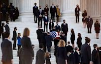 <p>People watch as the casket of the late US Supreme Court Justice Ruth Bader Ginsburg arrives at the US Supreme Court in Washington, DC, September 23, 2020.</p>