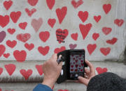 A woman takes a picture on her phone as people paint red hearts marking the completion of the approximately 150,000 hearts being painted onto the National Covid Memorial Wall to commemorate all those who have died of coronavirus, on the Thames Embankment opposite the Houses of Parliament in London, Thursday, April 8, 2021. Bereaved families want the wall of painted hearts to remain a site of national commemoration and are asking the Prime Minister to help make the memorial permanent. (AP Photo/Frank Augstein)