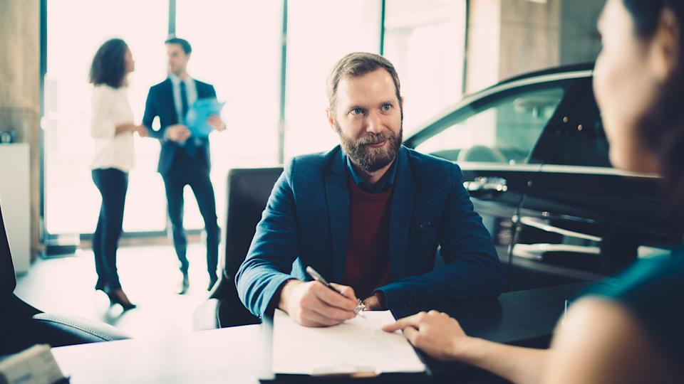 Businessman signing documents for buying luxury car.