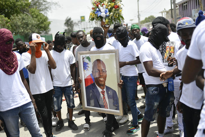 """Members of the gang led by Jimmy Cherizier, alias Barbecue, a former police officer who heads a gang coalition known as """"G9 Family and Allies,"""" carry a photo of slain President Jovenel Moise during a march to demand justice for his murder, in La Saline neighborhood of Port-au-Prince, Haiti, Monday, July 26, 2021. Moise was assassinated on July 7 at his home. (AP Photo/Matias Delacroix)"""