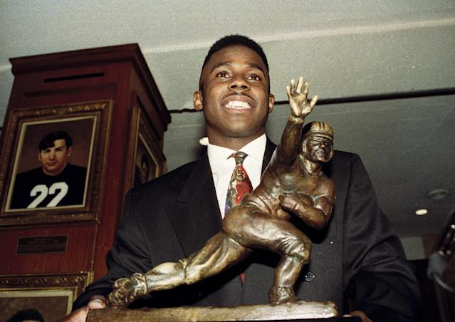 FILE - In this Dec. 14, 1991 file photo, University of Michigan wide receiver Desmond Howard poses with the Heisman Trophy at New York's Downtown Athletic Club. On Tuesday, April 1, 2014, it was announced that Howard will get the copyright to a famous photo of him in a Heisman Trophy pose after scoring a touchdown against Ohio State in 1991. Attorneys for Howard and photographer Brian Masck announced the agreement. Masck still is expected to benefit from commercial use of the photo, which was taken when Howard played for Michigan. (AP Photo/Mark Lennihan, File)