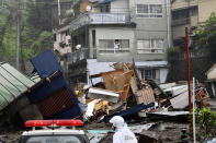 Houses are damaged by mudslide following heavy rain at Izusan district in Atami, west of Tokyo, Saturday, July 3, 2021. A powerful mudslide carrying a deluge of black water and debris crashed into rows of houses in a town west of Tokyo following heavy rains on Saturday, leaving multiple people missing, officials said. (Kyodo News via AP)