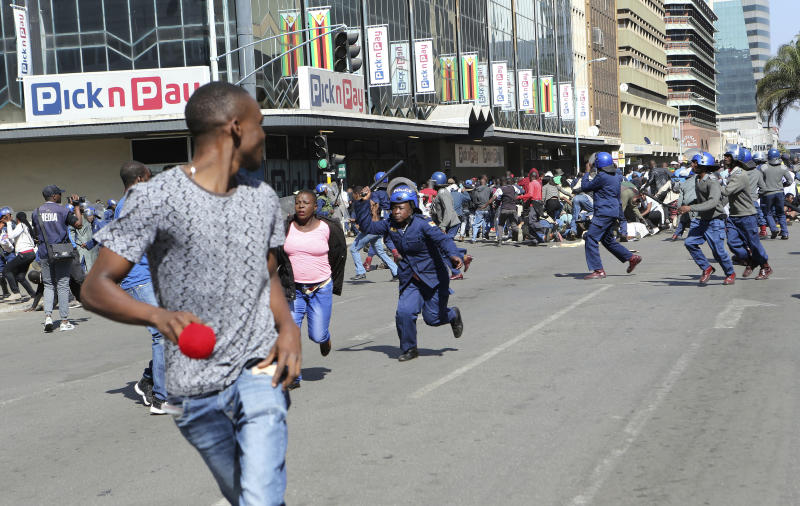 Riot police arrest and forcibly apprehend protestors during protests in Harare, Friday, Aug. 16, 2019. The main opposition Movement For Democratic Change party is holding protests over deteriorating economic conditions in the country as well as to try and force Zimbabwean President Emmerson Mnangagwa to set up a transitional authority to address the crisis and organize credible elections. (AP Photo/Tsvangirayi Mukwazhi)