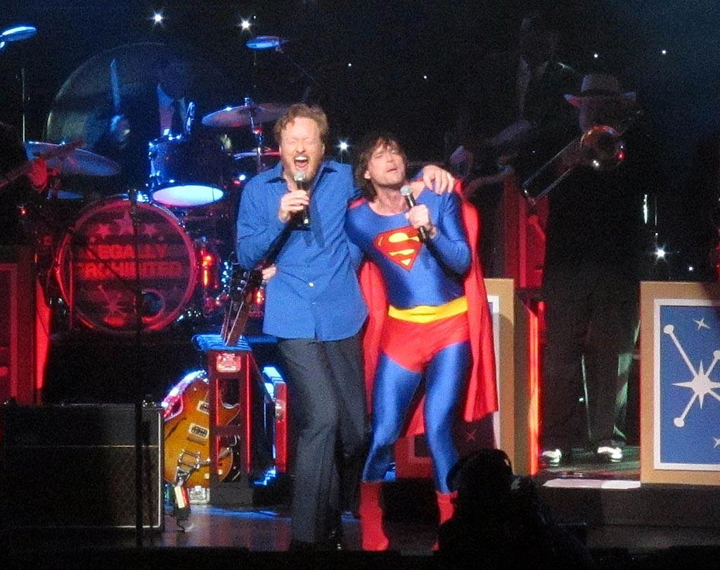"""Conan O'Brien had a surprise guest star at his stand up show -- """"The Legally Prohibited From Being Funny On Television Tour"""" -- in LA Sunday night. When the comedian launched into Five for Fighting's """"Superman (It's Not Easy),"""" he was joined by a superhero-clad Jim Carrey. The pair hammed it up during the <a href=""""http://www.youtube.com/watch?v=DxPEVe5Ih2M"""" target=""""new"""">hilarious duet</a>, with Conan showing off some awkward dance moves and Carrey hitting the high notes (almost). <a href=""""http://www.splashnewsonline.com"""" target=""""new"""">Splash News</a> - April 25, 2010"""