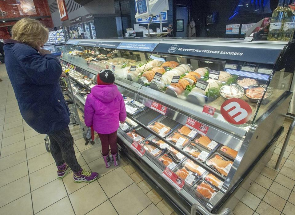 A customer and a little girl look at the seafood counter at a Metro store in Ste-Therese, Que