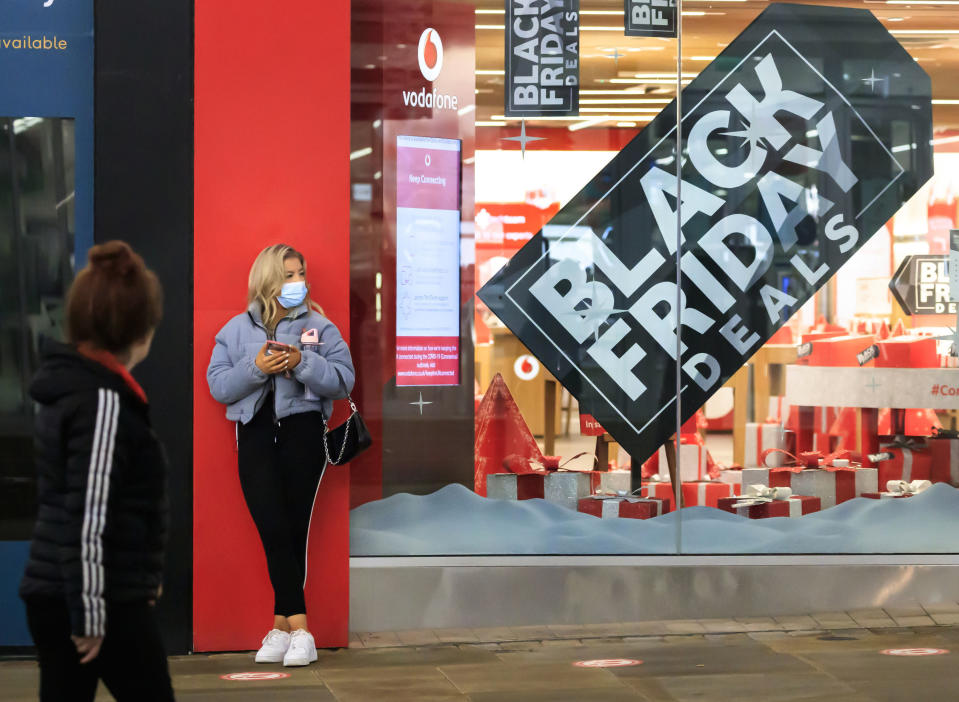 A woman next to a Black Friday poster in the window of a mobile phone store in Manchester city centre, England, although most stores remain closed Saturday Nov. 28, 2020. A four-week national lockdown to curb the spread of coronavirus is still restricting civil liberties and will put more pressure on shops to attract customers back to shopping streets when restrictions are relaxed in the run-up to Christmas. (Danny Lawson/PA via AP)