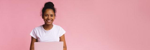 Student sitting cross-legged with an open laptop in her lap against a pink background