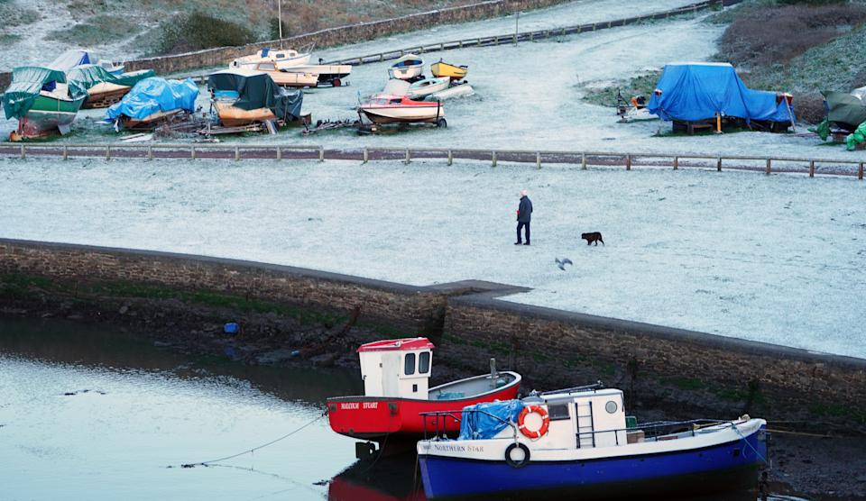 A man walks a dog in a light dusting of overnight snow at Seaton Sluice on the North East coast. Picture date: Sunday April 11, 2021.