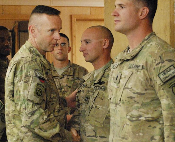 In this photo taken on Nov. 24, 2011, and released by the U.S. Army, Army Capt. Joseph M. Lapoint, second from right, executive officer for Charlie Company, 1st Battalion, 24th Infantry Regiment, is congratulated for his Combat Infantryman Badge awarded by Brig. Gen. Jeffrey A. Sinclair, left, Deputy Commanding General, 82nd Airborne Division, at Forward Operating Base Lagman, in Zabul province, Afghanistan. Sinclair, who served five combat tours, is headed to trial following a spate of highly publicized military sex scandals involving high-ranking officers that has triggered a review of ethics training across the service branches. (AP Photo/U.S. Army, Sgt. Francis O'Brien)