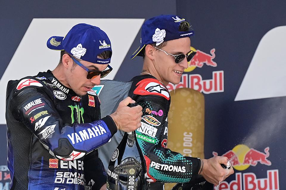 Monster Energy Yamaha's second-placed Spanish rider Maverick Vinales (L) and Petronas Yamaha SRT's French winner Fabio Quartararo celebrate on the podium after the MotoGP race during the Andalucia Grand Prix at the Jerez race track in Jerez de la Frontera on July 26, 2020. (Photo by JAVIER SORIANO / AFP) (Photo by JAVIER SORIANO/AFP via Getty Images)