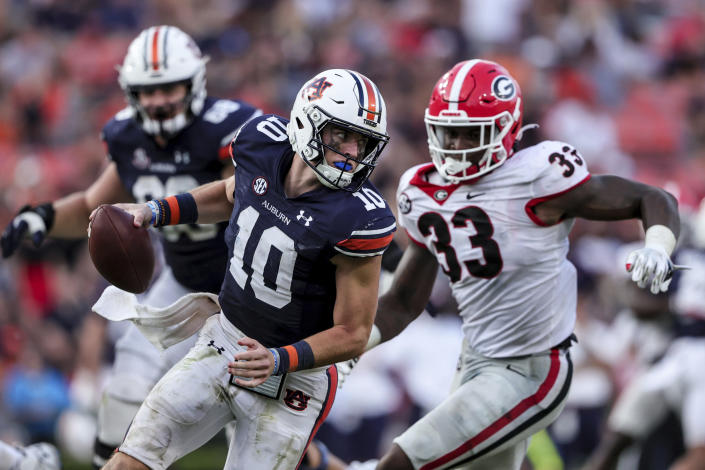 Auburn quarterback Bo Nix (10) tries to elude the pressure from Georgia linebacker Robert Beal Jr. (33) during the second half of an NCAA college football game Saturday, Oct. 9, 2021, in Auburn, Ala. (AP Photo/Butch Dill)