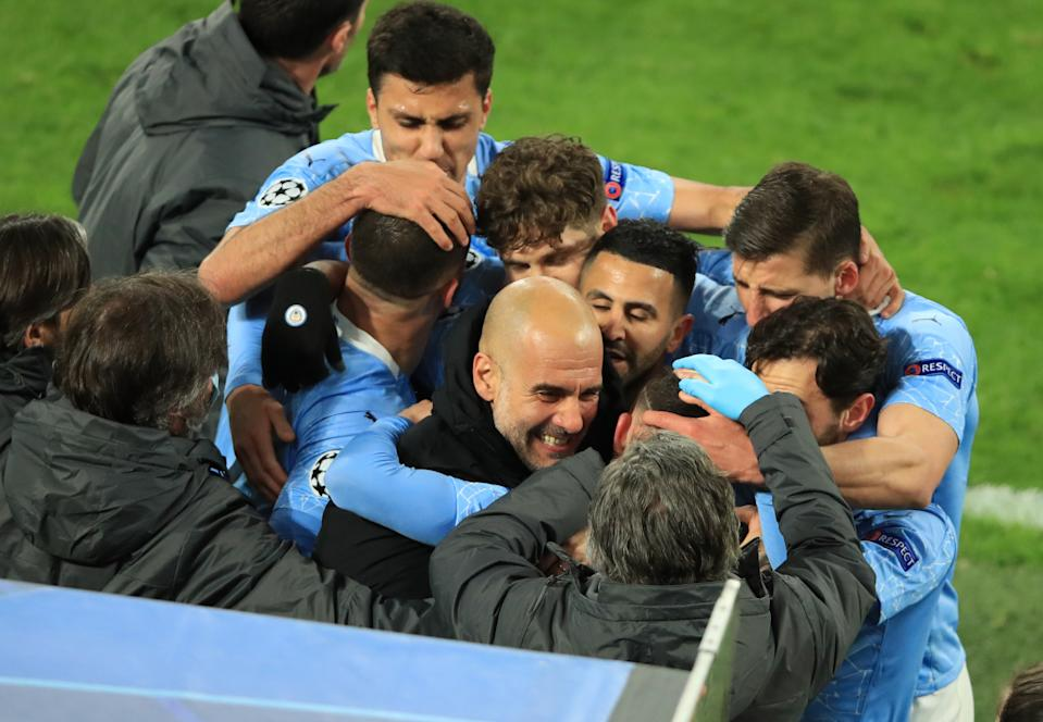 Manchester City players celebrating their second goal with manager Pep Guardiola.