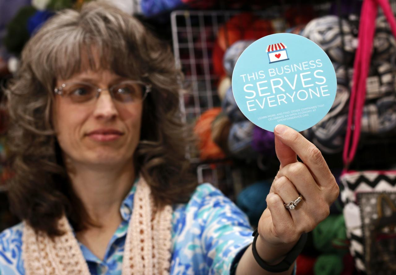 """Elizabeth Ladd, owner of River Knits Fine Yarns, poses while holding up a """"This businesses serves everyone"""" sticker she plans to place outside her business in downtown Lafayette, Indiana March 31, 2015.  Indiana's Republican Governor Mike Pence, responding to national outrage over the state's new Religious Freedom Restoration Act, said on Tuesday he will """"fix"""" it to make clear businesses cannot use the law to deny services to same-sex couples.   REUTERS/Nate Chute"""