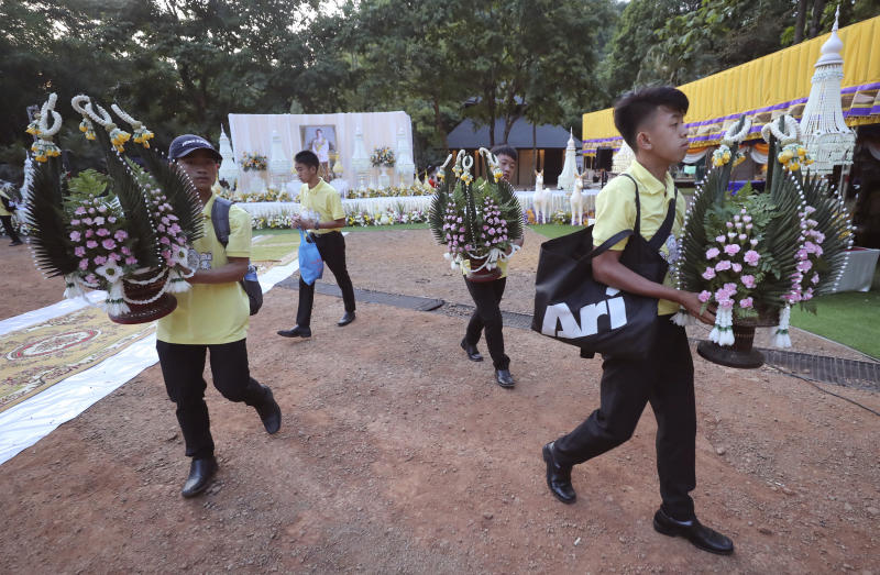 Members of the Wild Boars soccer team who were rescued from a flooded cave, carry flowers for a religious ceremony near the Tham Luang cave in Mae Sai, Chiang Rai province, Thailand Monday, June 24, 2019. The 12 boys and their coach attended a Buddhist merit-making ceremony at the Tham Luang to commemorate the one-year anniversary of their ordeal that saw them trapped in a flooded cave for more than two weeks. (AP Photo/Sakchai Lalit)
