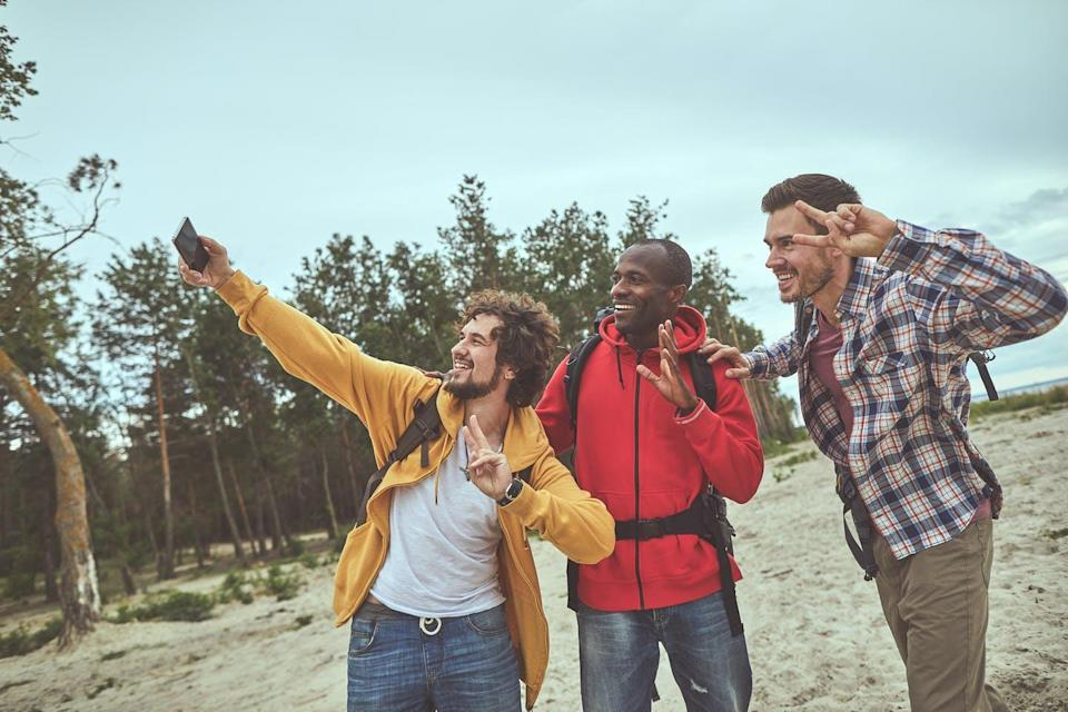 Three men pose for a selfie on a beach while hiking.