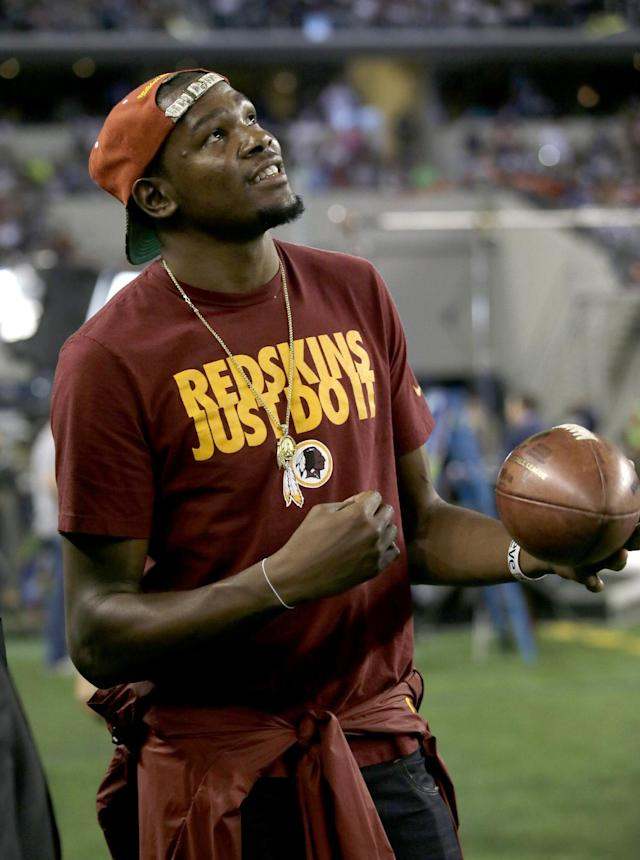 Oklahoma City Thunder's Kevin Durant stands on the sideline peering up at the large video screen playing with a football as the Redskins and Dallas Cowboys warm up before an NFL football game, Sunday, Oct. 13, 2013, in Arlington, Texas. (AP Photo/Tim Sharp)