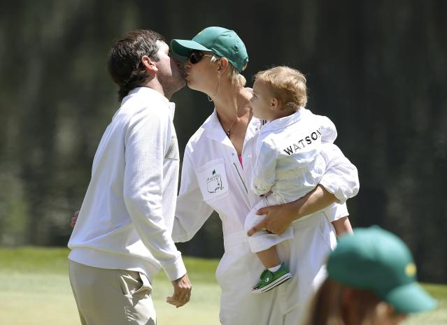 U.S. golfer Bubba Watson (L) kisses his wife Angie (C), who is holding their son Caleb, on the ninth green during the Par 3 Contest ahead of the 2014 Masters golf tournament at the Augusta National Golf Club in Augusta, Georgia April 9, 2014. REUTERS/Jim Young (UNITED STATES - Tags: SPORT GOLF)