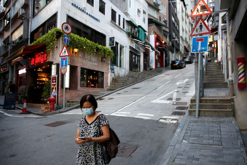 FILE PHOTO: A woman wears a surgical mask while walking at Central following the coronavirus disease (COVID-19) outbreak in Hong Kong,