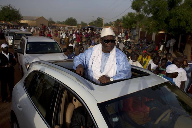 Presidential candidate Ibrahim Boubacar Keita, known by his initials 'IBK,' stands out through his car as he leaves a campaign rally in Bandiagara, Dogon Country, Mali, Sunday, July 21, 2013. Candidates are traveling the country holding rallies as they head into the final week of campaigning ahead of Mali's July 28 presidential vote. (AP Photo/Rebecca Blackwell)