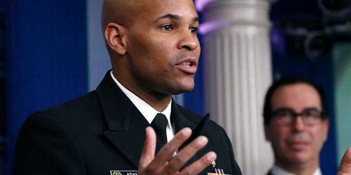 US Surgeon General Jerome Adams speaks at a coronavirus briefing at the White House on March 14, 2020, as Treasury Secretary Steven Mnuchin listens in the background.
