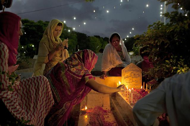 <p>People light candles and offer prayers at a grave of their relative in a local graveyard of Karachi, Pakistan on the occasion of Shab-e-Barat, June 13, 2014, 2014. (AP Photo/Shakil Adil) </p>