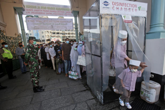 Muslims walk through a disinfection chamber installed to curb the spread of coronavirus outbreak as they enter Al Mashun Great Mosque compound to attend an Eid al-Fitr prayer in Medan, North Sumatra, Indonesia, Thursday, May 13, 2021. (AP Photo/Binsar Bakkara)
