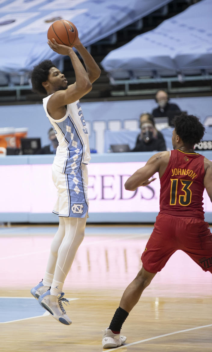 North Carolina's Kerwin Walton (24) launches a three-point shot over Louisville's David Johnson (13) in the first half of an NCAA college basketball game Saturday, Feb. 20, 2021, at the Smith Center in Chapel Hill, N.C. (Robert Willett/The News & Observer via AP)