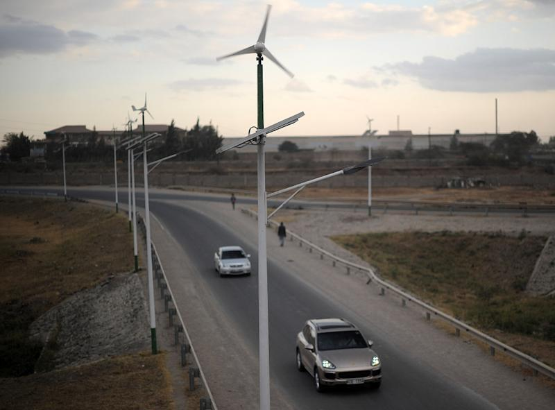 Street lamps powered by wind and solar energy line the side of a road in Kenya on August 19, 2015 (AFP Photo/Tony Karumba)
