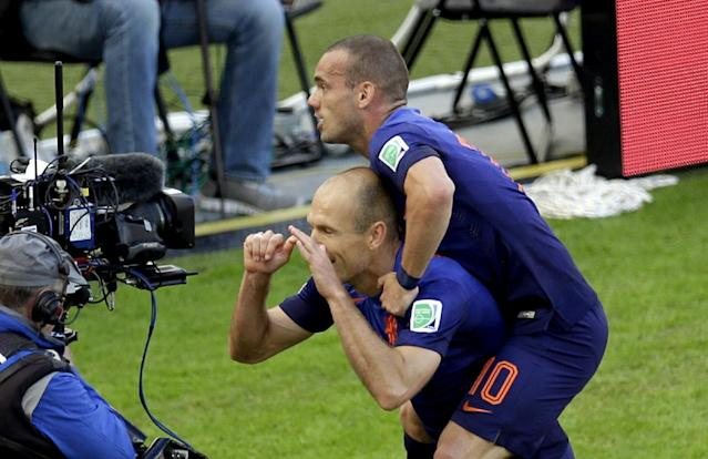 Netherlands' Arjen Robben, left, is congratulated by his teammate Wesley Sneijder after scoring the opening goal during the group B World Cup soccer match between Australia and the Netherlands at the Estadio Beira-Rio in Porto Alegre, Brazil, Wednesday, June 18, 2014. (AP Photo/Michael Sohn)