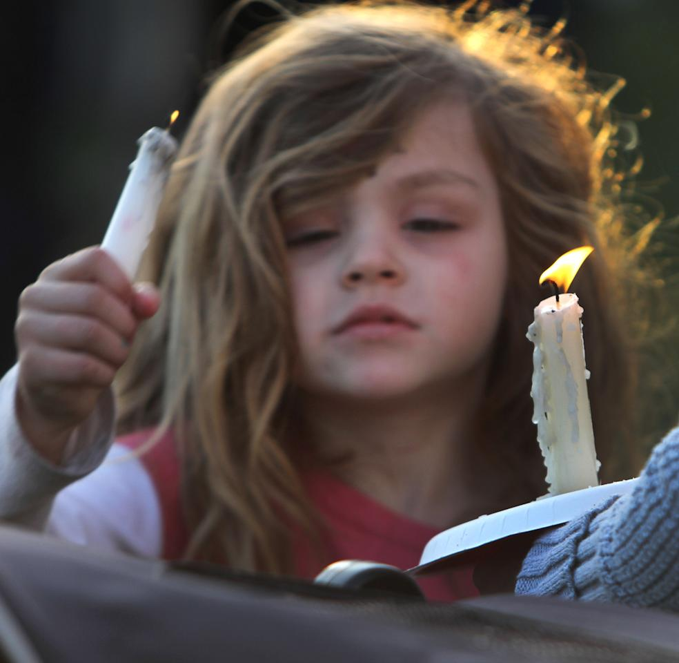 Addie Delisle lights her candle during a vigil for slain Police chief Michael Maloney, Friday, April 13, 2012 in Greenland, N.H. Maloney was trying to serve a search warrant Thursday night when a suspect opened fire, killing the 48-year-old chief, injuring four officers from other departments, and plunging the southeastern New Hampshire community of Greenland into a grief that residents say they won't soon get over.(AP Photo/Jim Cole)