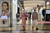 People walk in Mall of the Emirates, in Dubai, United Arab Emirates, Thursday, April 15, 2021. The Middle East's largest operator of malls, Majid Al Futtaim expects revenue and earnings to climb back to pre-pandemic levels by the end of next year and is moving full steam ahead with plans to develop its biggest mall ever. (AP Photo/Kamran Jebreili)