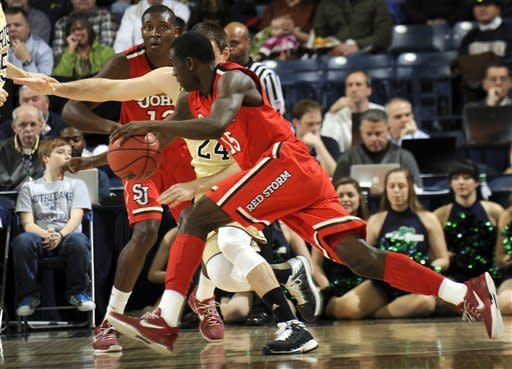 St. John's guard Sir'Dominic Pointer drives the lane past Notre Dame guard Pat Connaughton during the first half of an NCAA college basketball game, Tuesday, March 5, 2013 in South Bend, Ind. Looking on in the background is St. John's guard Chris Obekpa. (AP Photo/Joe Raymond)