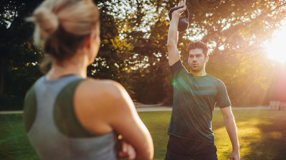 Healthy young man with female trainer exercising with kettlebell in the park.