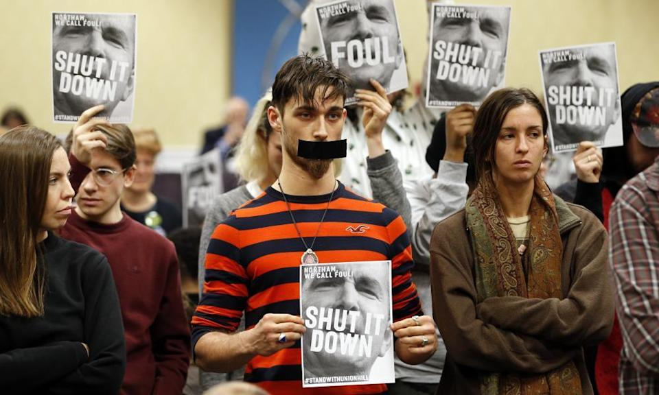 Protesters hold signs as they turn their backs on a meeting of the Virginia State Air Quality Control Board in Richmond, Va.