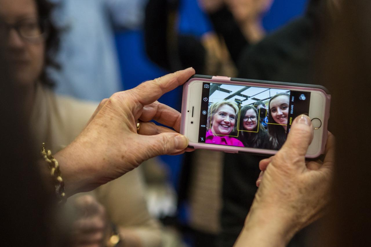 <p>Democratic presidential candidate Hillary Clinton is seen on a cellphone screen taking a selfie with audience members following a campaign organizing event at Eagle Heights Elementary on Jan. 23, 2016 in Clinton, Iowa. (Photo: Brendan Hoffman/Getty Images)</p>