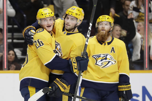 Nashville Predators center Calle Jarnkrok (19), of Sweden, celebrates with Daniel Carr (26) and Ryan Ellis, right, after Jarnkrok scored a goal against the Tampa Bay Lightning in the second period of an NHL hockey game Tuesday, Dec. 3, 2019, in Nashville, Tenn. (AP Photo/Mark Humphrey)
