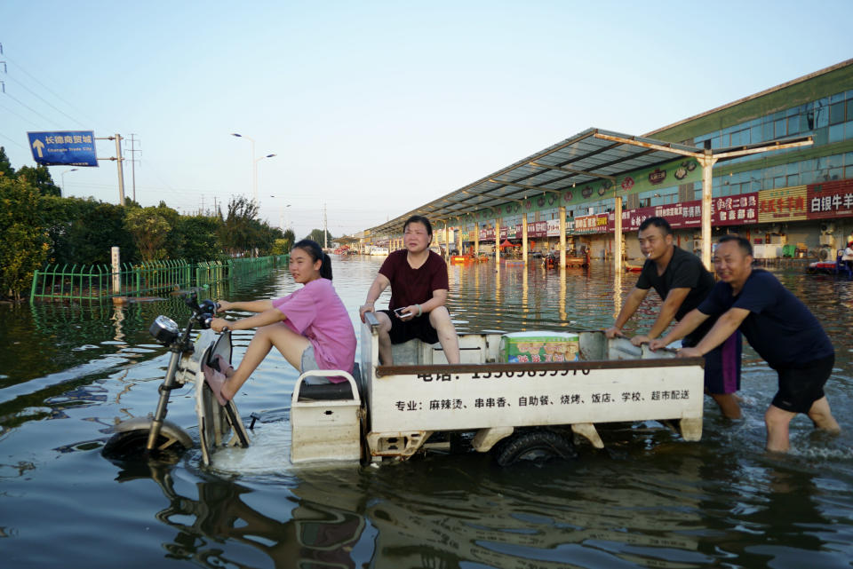 Shopkeepers at the Yubei Agricultural and Aquatic Products World leave the market on a motor tricycle in Xinxiang in central China's Henan Province, Monday, July 26, 2021. Record rain in Xinxiang last week left the produce and seafood market soaked in water. Dozens of people died in the floods that immersed large swaths of central China's Henan province in water. (AP Photo/Dake Kang)